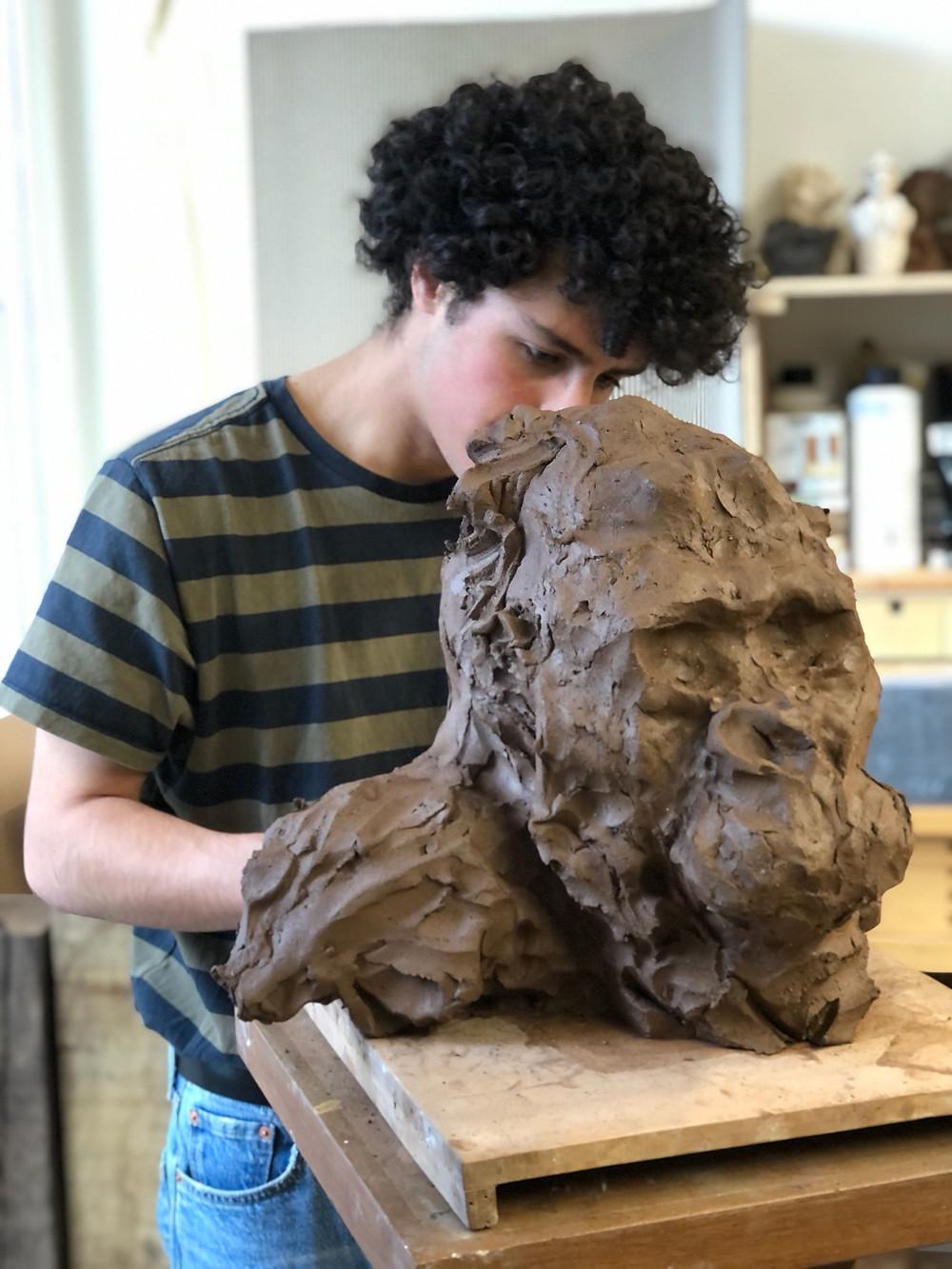 Photo portrait de Ronceval, jeune sculpteur céramique. Artiste. Céramique animalière. Travaillant sur une œuvre : un gorille