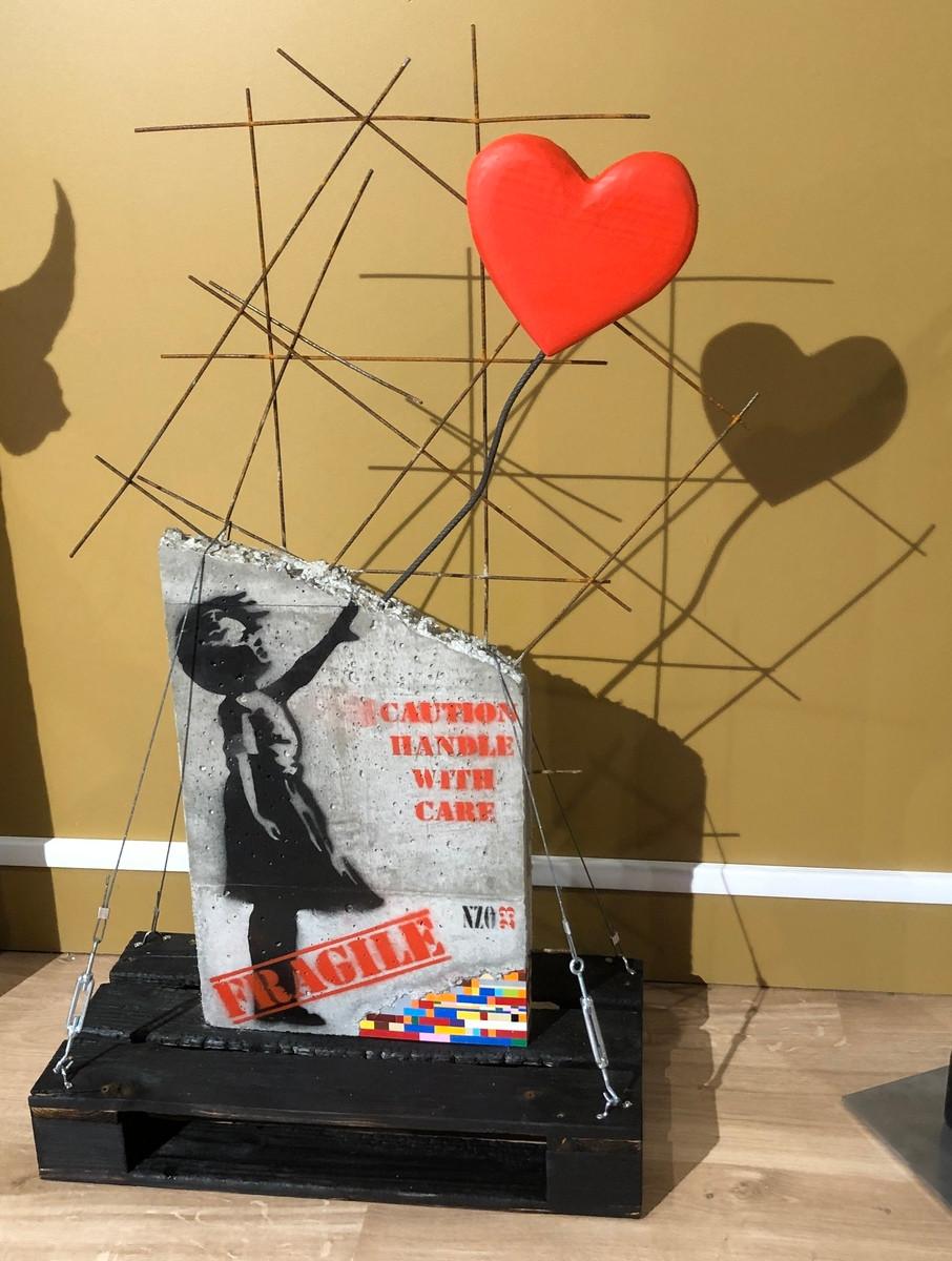 Oeuvre béton avec incrustation de légo faite par NZO23. Hommage à Banksy, la petite fille au ballon rouge. Palette de bois brulé et bloc de béton feraillé