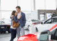 Couple-hugging-in-car-dealership-xlarge.