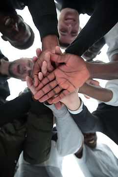 bottom view. a group of diverse young people joining their hands together.jpg