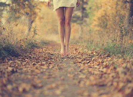 Image of woman walking on a leaf covered path.