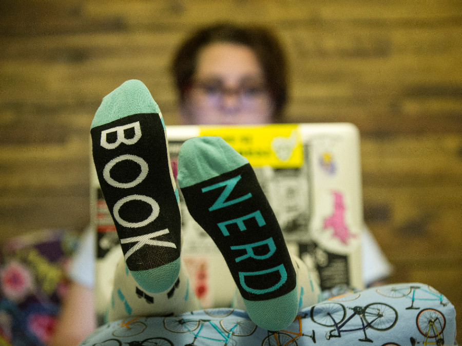 Amy Tipton holding computer with socks that say book nerd