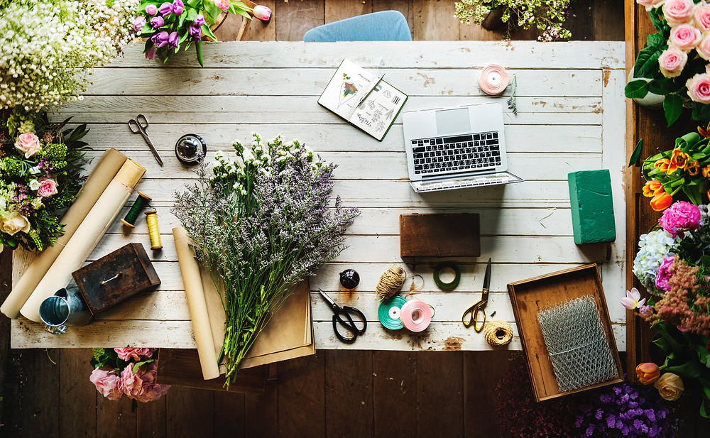 picture of gardening table with flowers, tools, and laptop