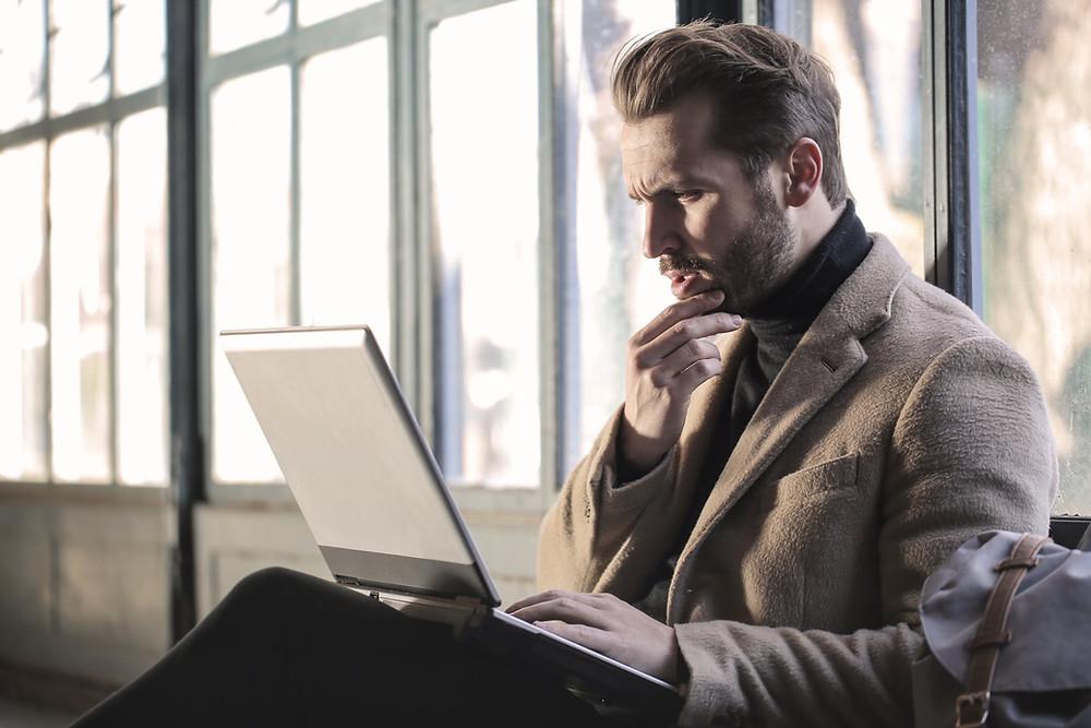 Man sitting down focusing on his laptop