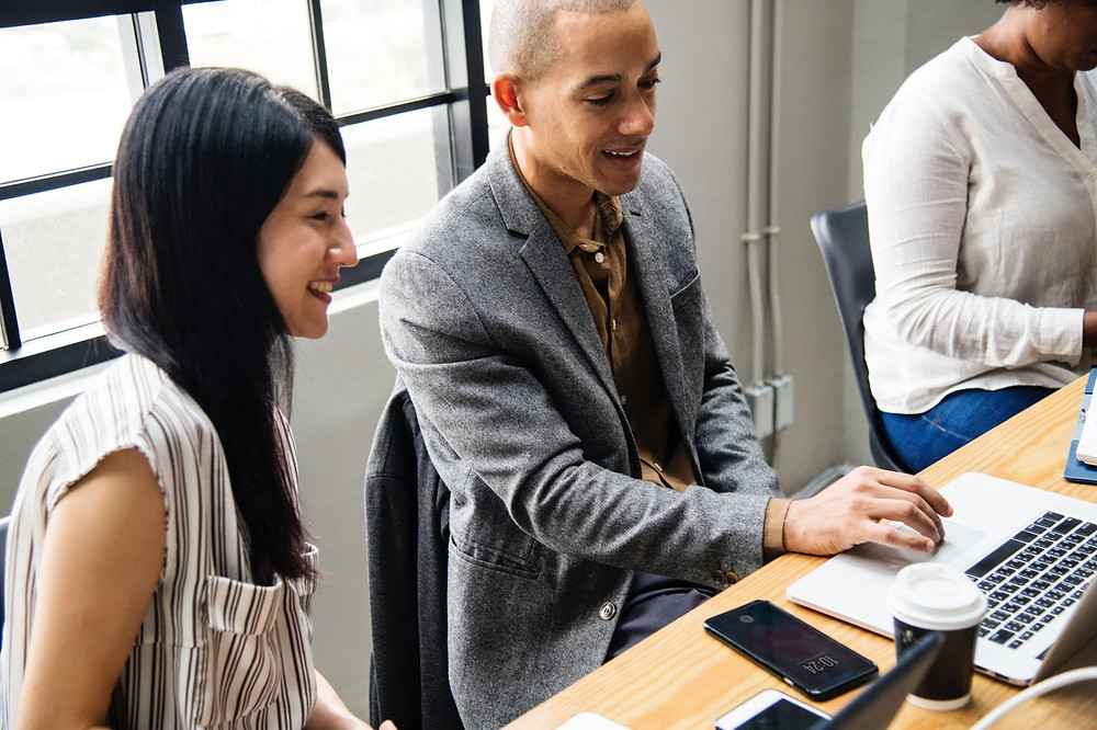 man and woman looking at computer during meeting
