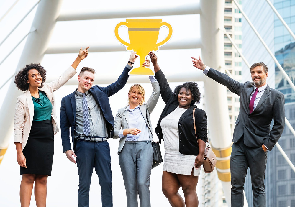 group of people holding up a paper trophy