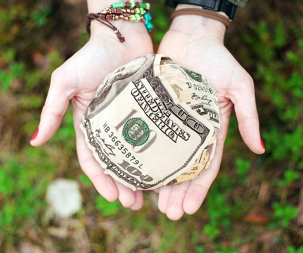 Hands holding a ball of money