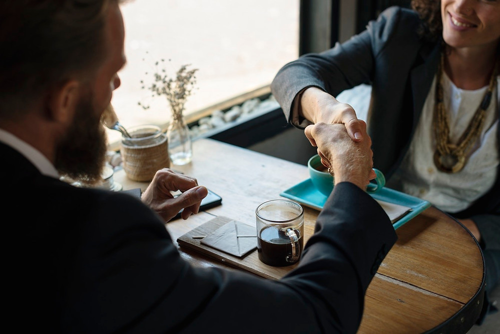 man and woman shaking hands during work meeting