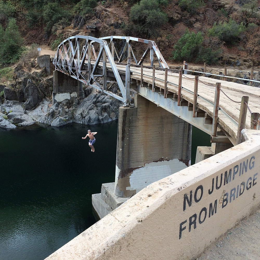 Picture of man jumping off of bridge into water
