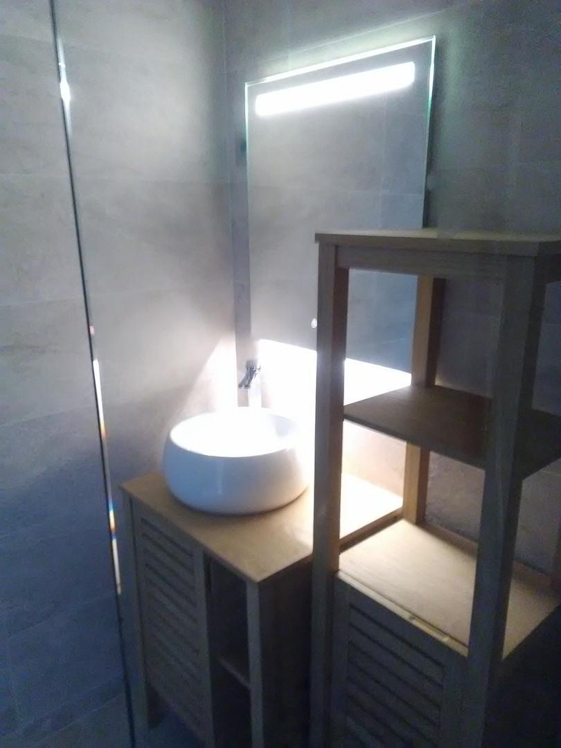 Miroir à leds tactile avec variateur d'intensité et de couleurs, vasque ronde et mitigeur céramique haut de gamme posés sur meubles bois.