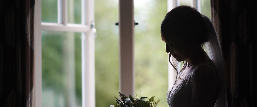Bride in window, looking at flowers