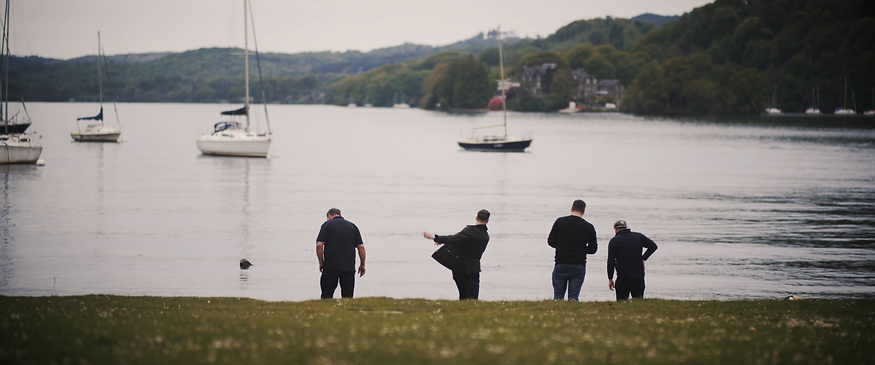 Grooms party go stone skimming on Lake Winderemere prep