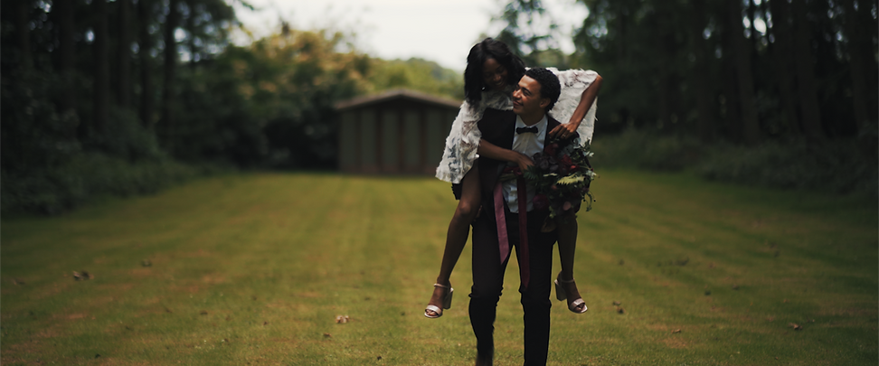 couple piggy back in a field after getting married