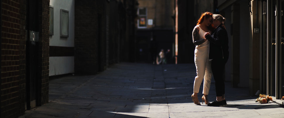 couple dancing in city centre alley after getting married