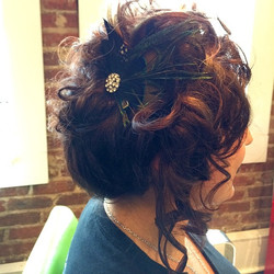 Tumbly asymmetric updo accented with a peacock feather