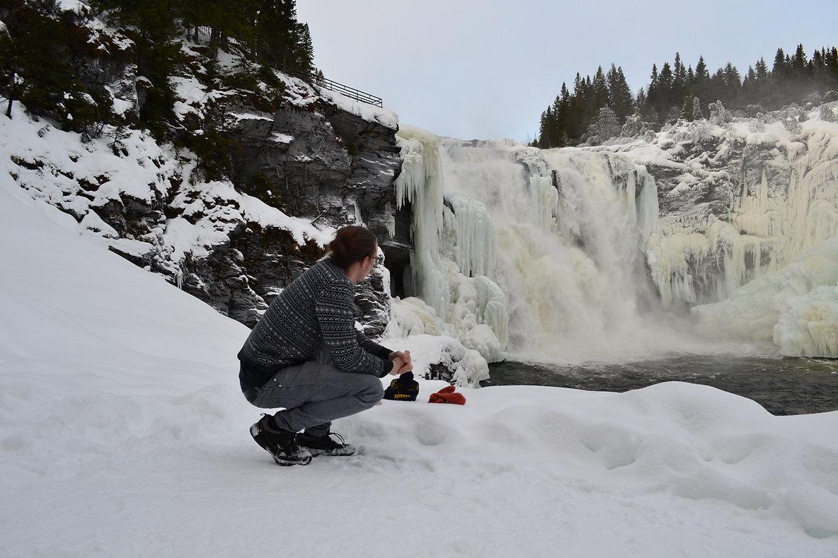 Schwedisch Foto von Tännforsen, Region Norrland. Ein Mann sitzt nebem dem gefrieren Fluss.