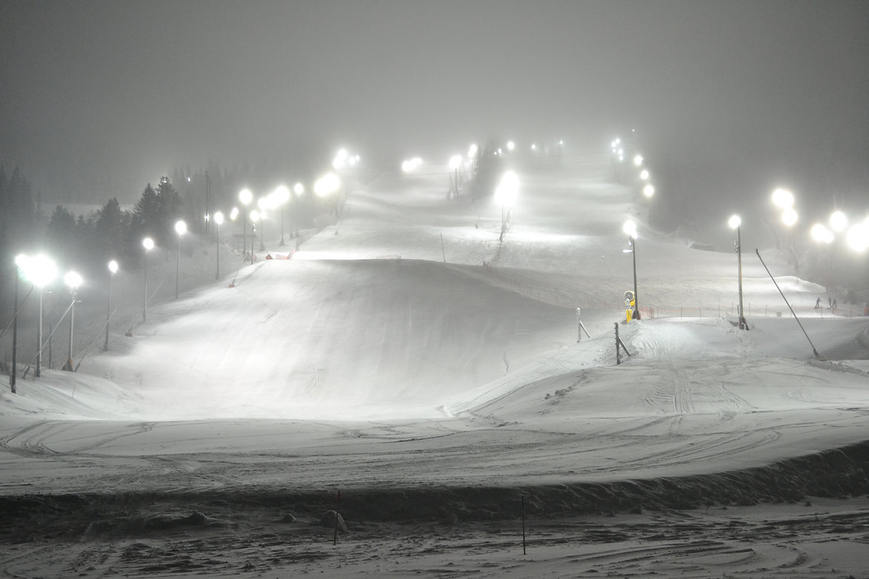 Schwedisch Foto von der Skipiste im dunkel. Skipiste ist aufgeleuchtet, Region Norrland.