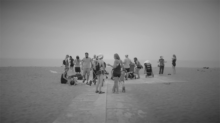 The participants of a summer group intensive for children with special needs and severe disabilities gather on a beach in Toronto with their families