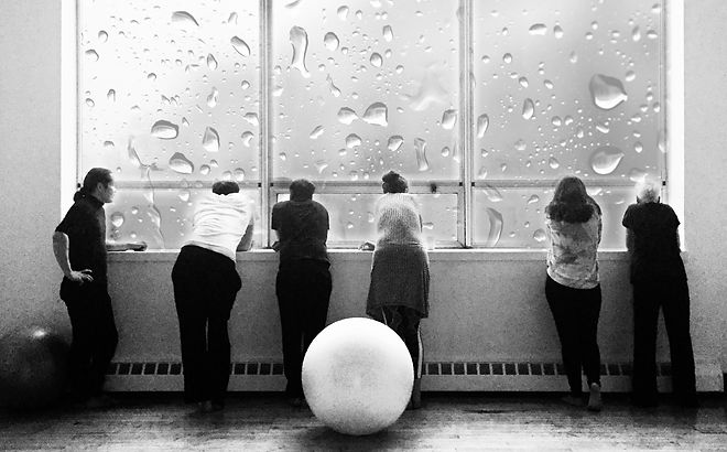The staff of the Spiral Movement Center gather at a window on a rainy day