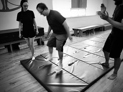 Down Syndrome adult jumping along a mat with instructors watching