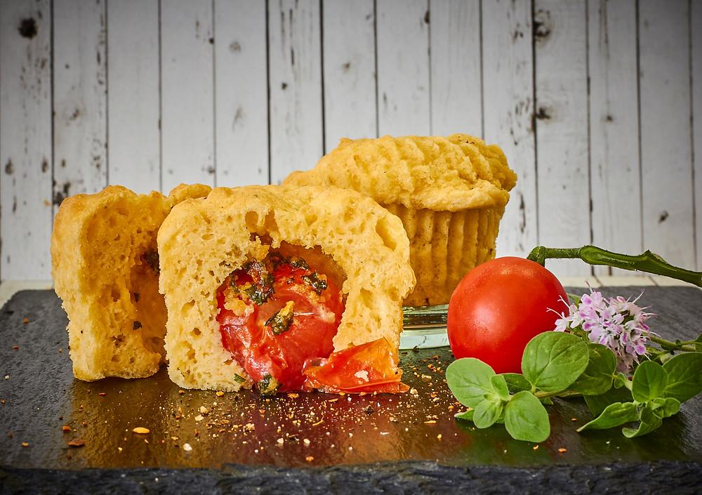 Parmesan-Muffins, gefüllt mit einer Kirschtomate.
