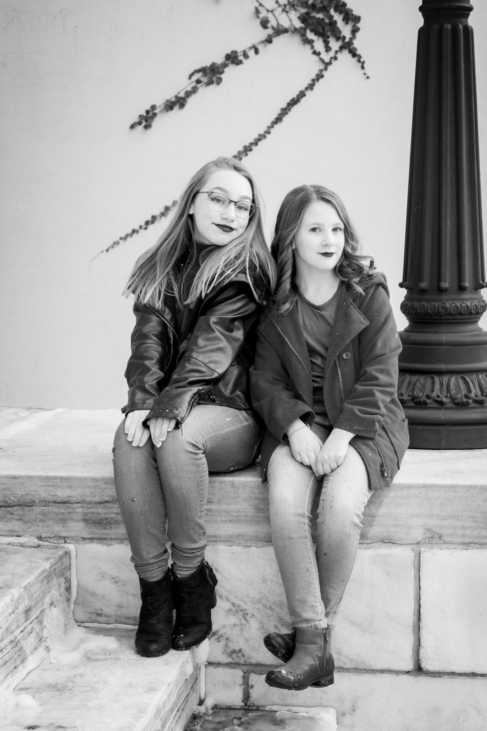 Two young girls sitting on steps at an art museum