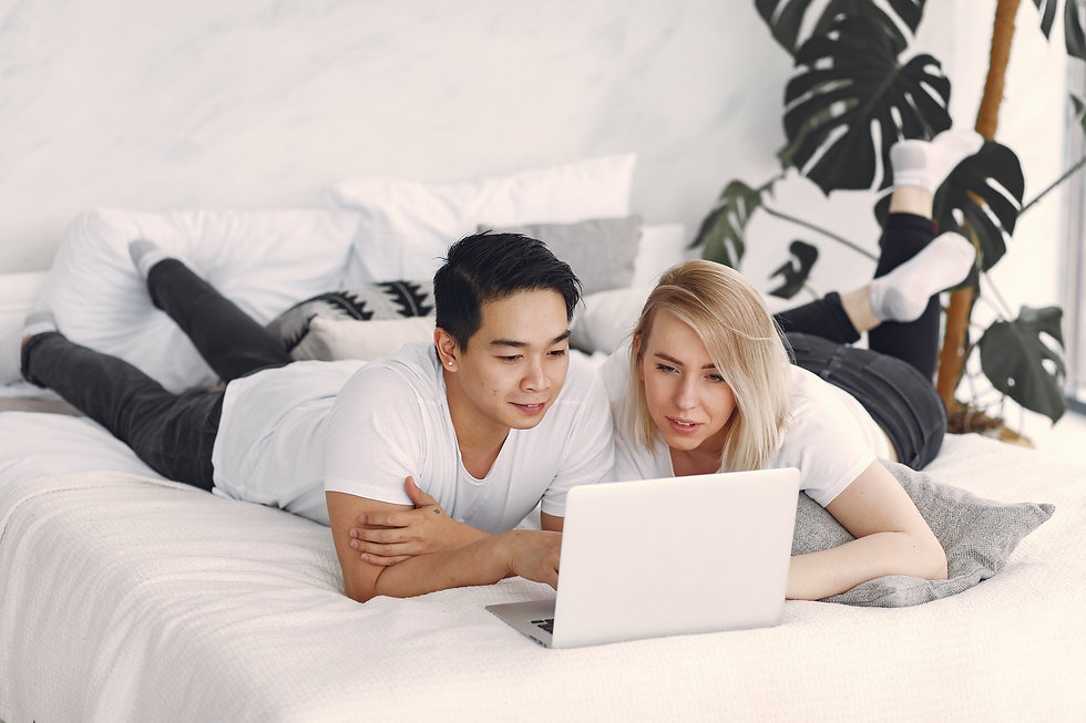 man-and-woman-on-bed-using-laptop-comput