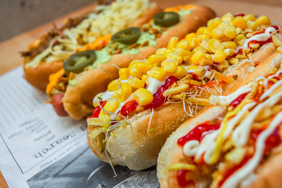 Four hot dogs full of diverse ingredient
