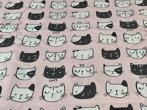 Cats faces on pale pink cotton jersey