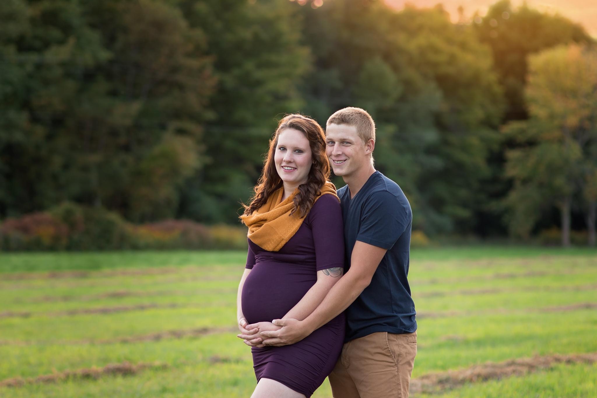 husband hugging pregnant wife