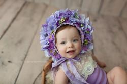baby girl in purple bonnet
