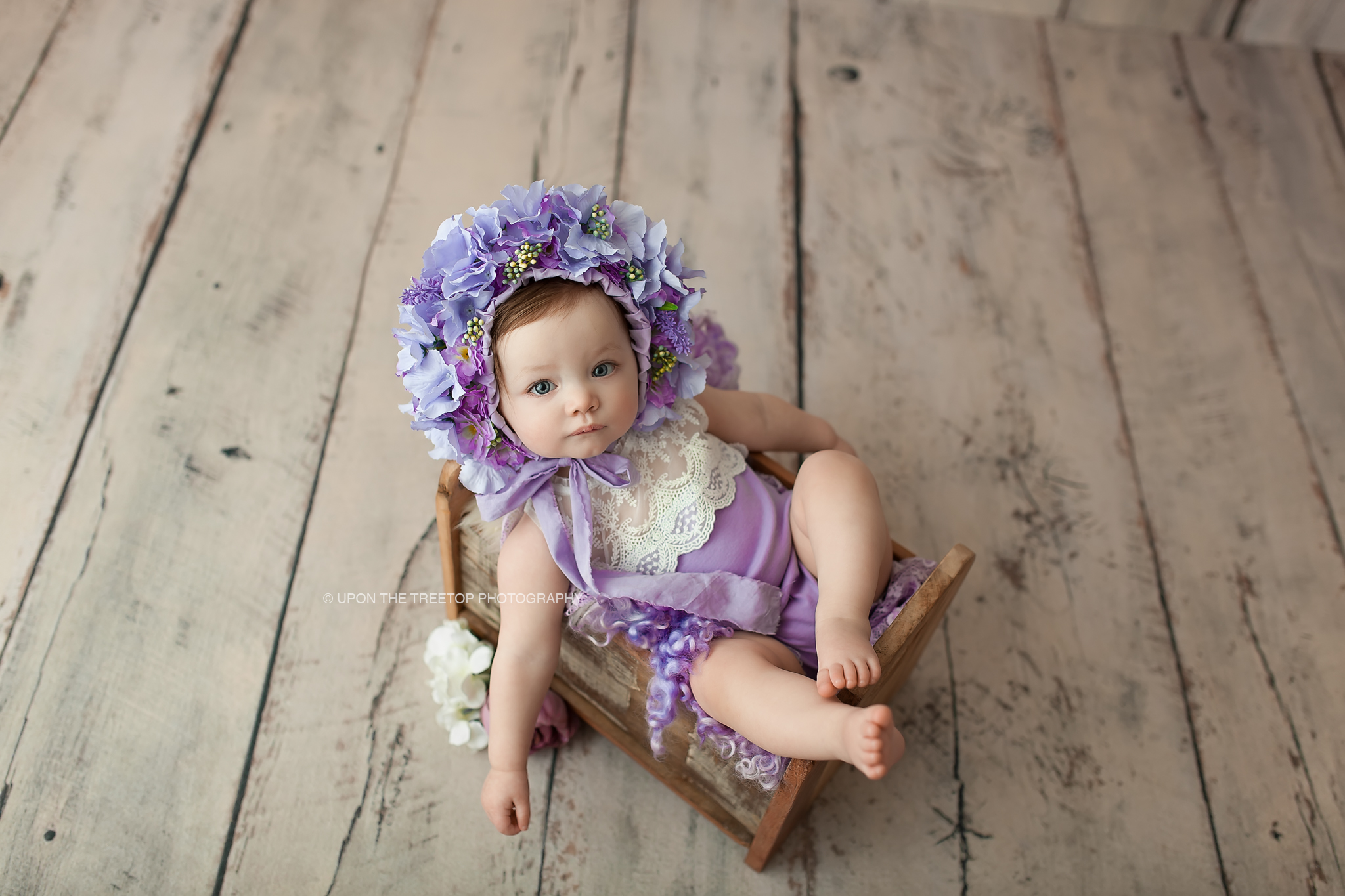 baby girl in purple flower bonnet