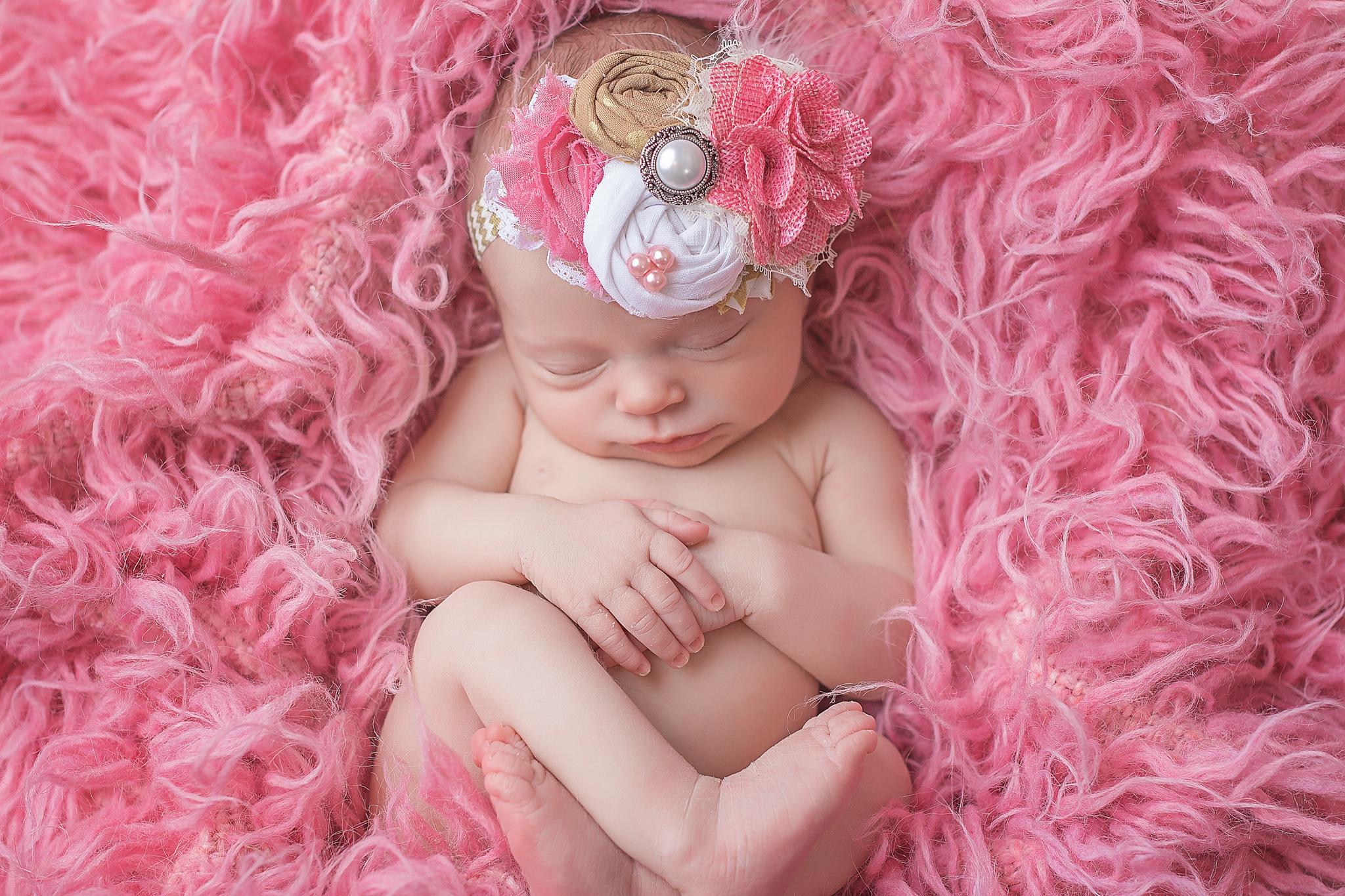 newborn on pink flokati