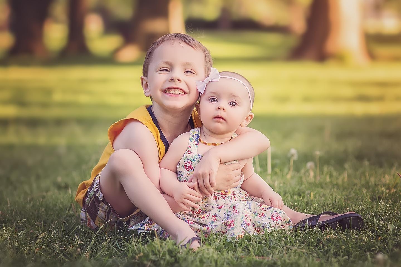 siblings outside smiling