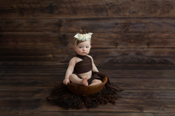 baby girl in wood bowl