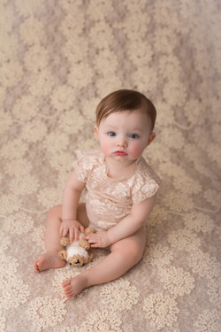 baby holding sheep stuffy