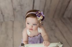 baby girl holding chair