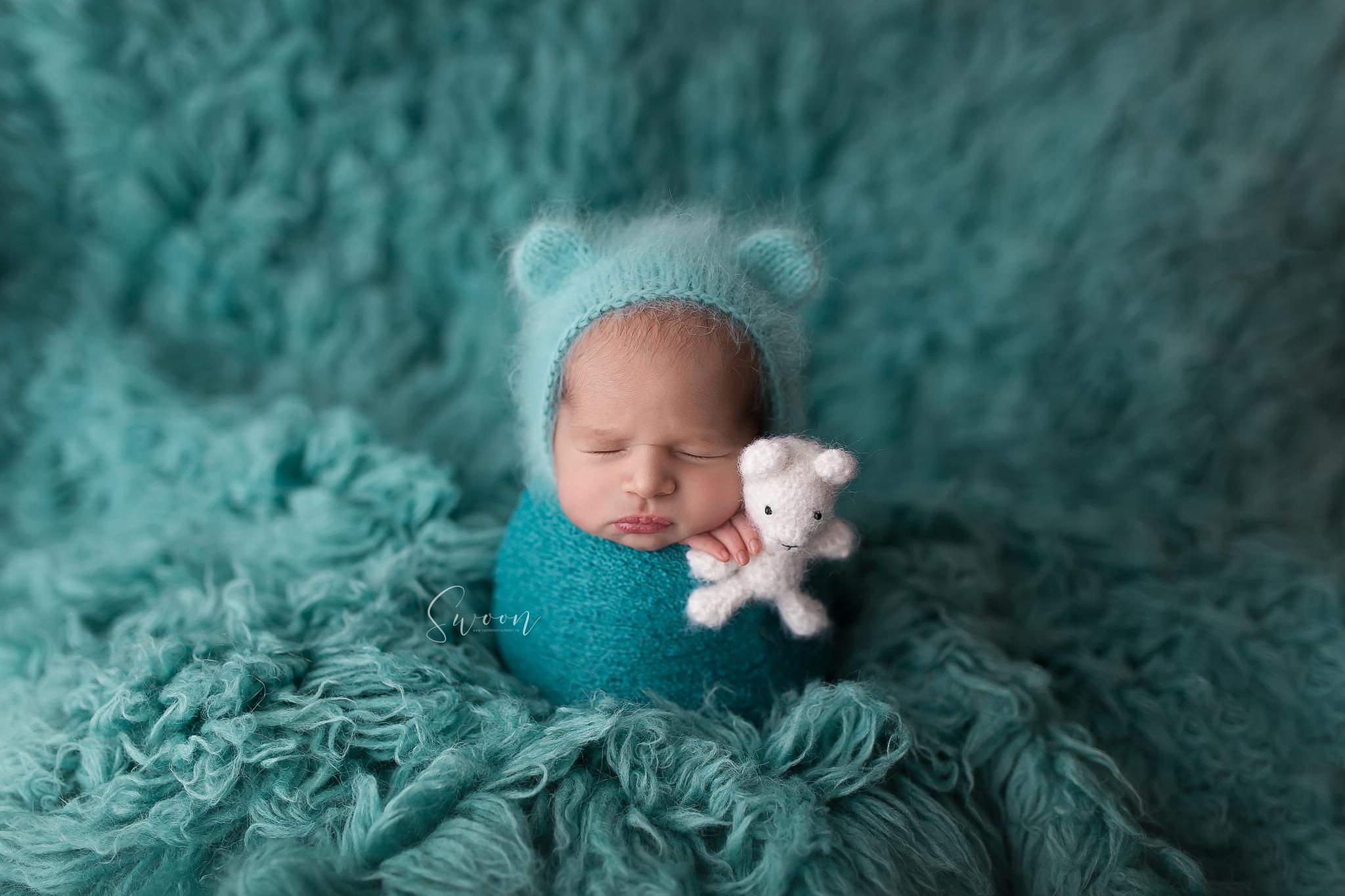 newborn on aqua flokati
