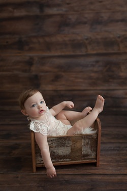 baby girl in wood bed prop