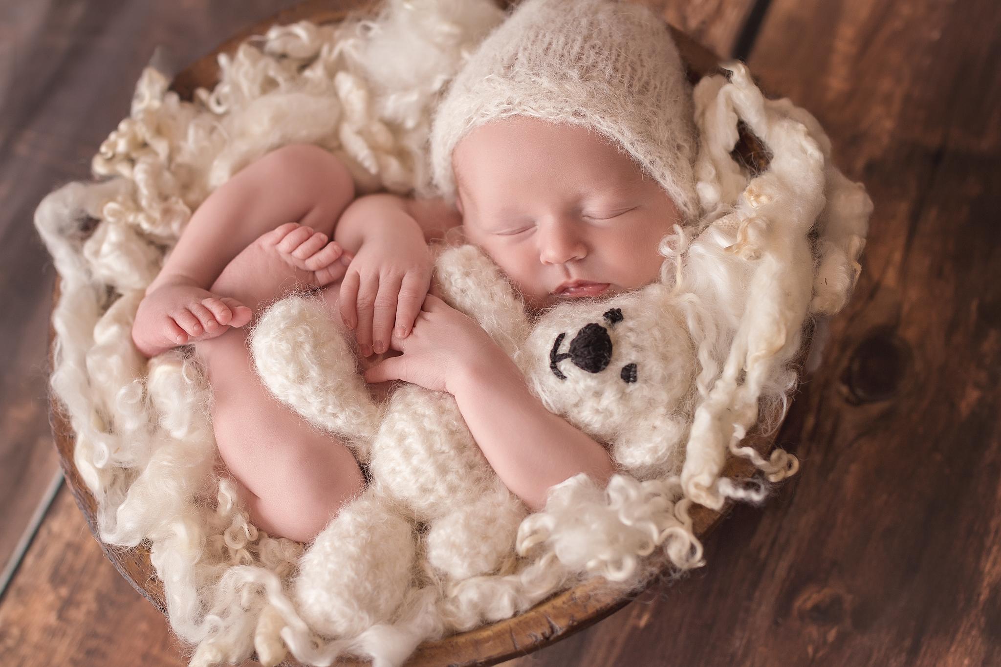 baby hugging bear