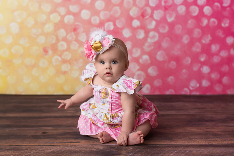 baby on yellow and pink polka dot
