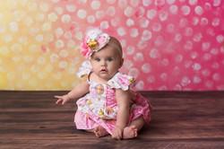 baby on yellow and pink polka dot