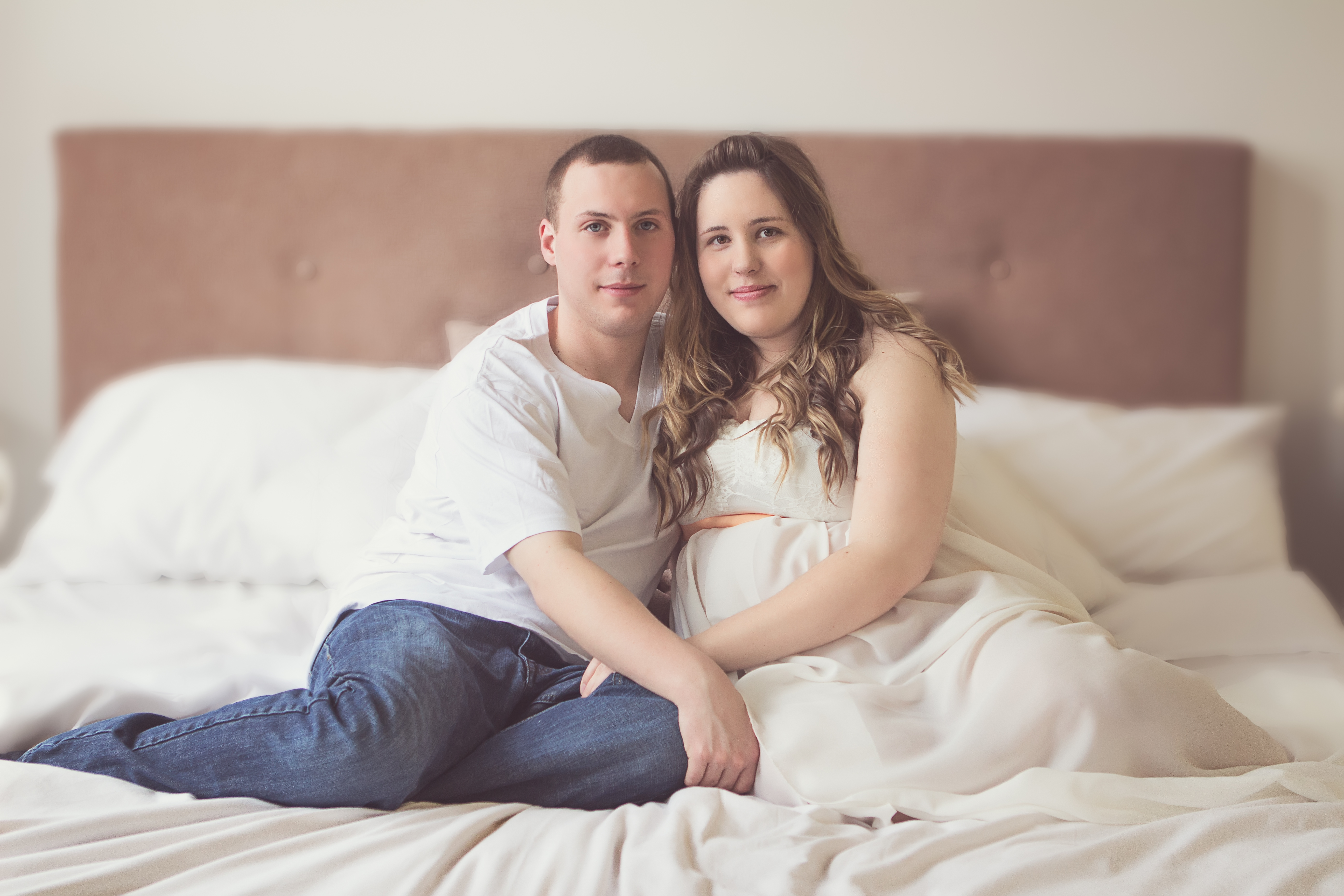 pregnant couple sitting on bed