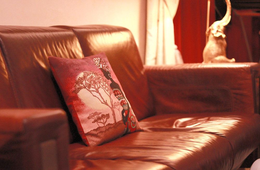 livingroom-home-interior-brown-sofa-couch-leather-red-african-pillow-gold-elephant-decor