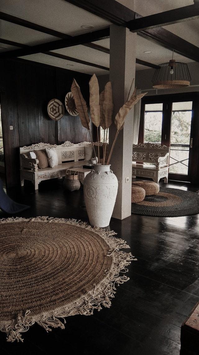 Rustic living room, black wooden floor, black walls, white decoration details and wicker carpet