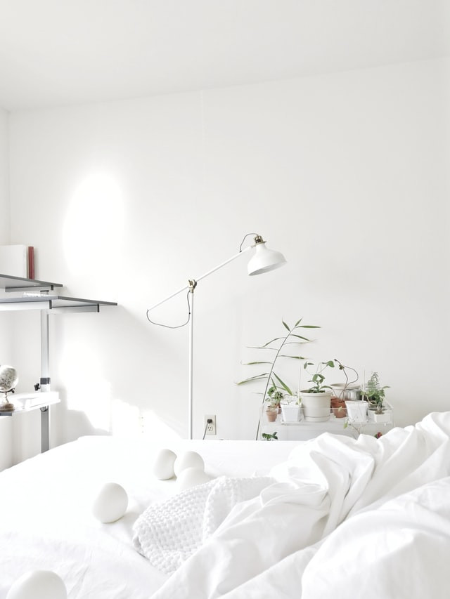 all-white-home-bedroom-white-wall-bed-plants-decor