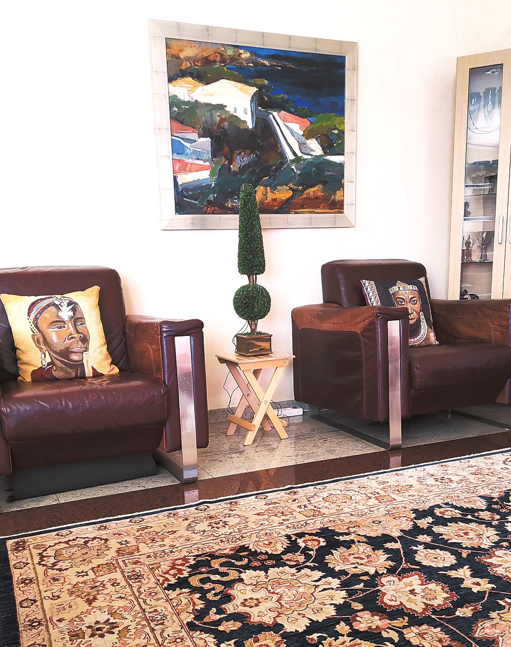 interior-livingroom-two-brown-leather-armchairs-african-style-pillows-tree-rug-home-decor
