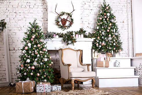 Christmas tree and a chair stands near the fireplace  and other holiday decorations in whi