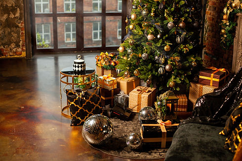 Close-up of a Christmas tree decorated with gold balls. Under the Christmas tree a large n