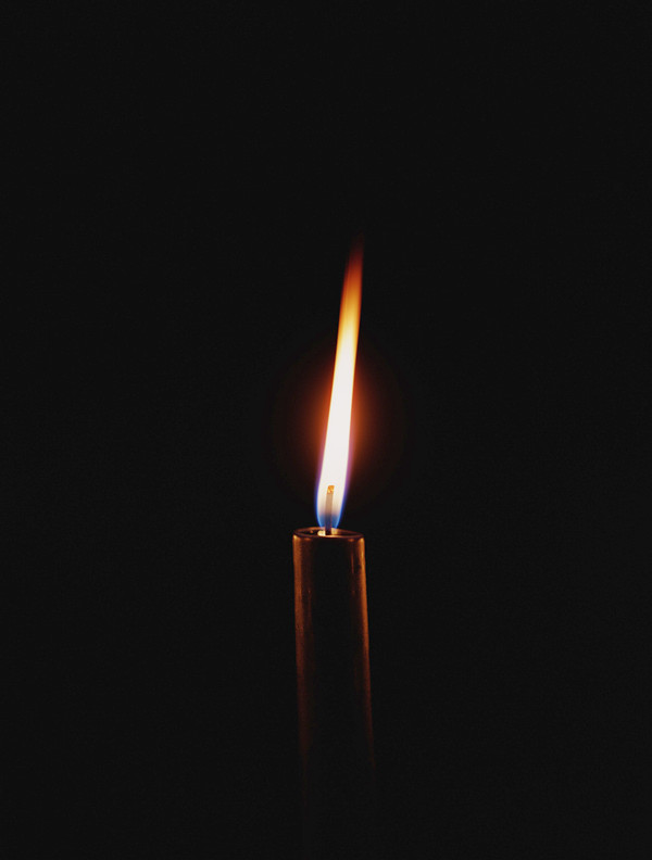 Lit candle in the darkness.